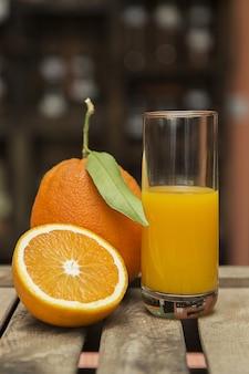 Primer plano de un vaso de jugo de naranja y naranjas frescas en una caja de madera con borrosa