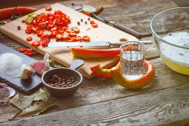 Primer plano de un vaso de vinagre y pimienta entera junto a un tablero con pimientos picados sobre una superficie de madera vieja