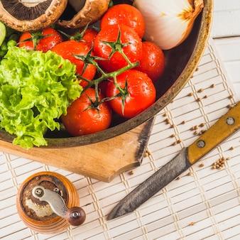 Primer plano de vegetales saludables; cuchillo; molinillo de especias en mantel