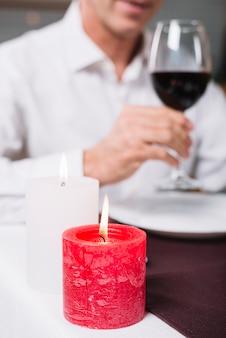 Primer plano de una vela durante una cena romántica.