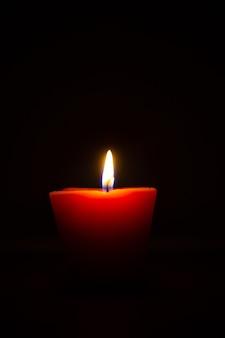 Primer plano de una vela encendida aislado sobre fondo negro.