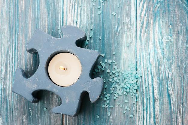 Primer plano de vela encendida azul y sal de baño