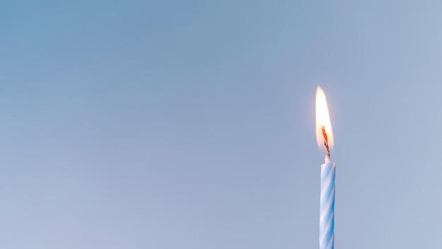 Primer plano de una vela iluminada sobre fondo azul