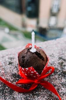 Primer plano de la vela en el pastel decorado con cinta roja