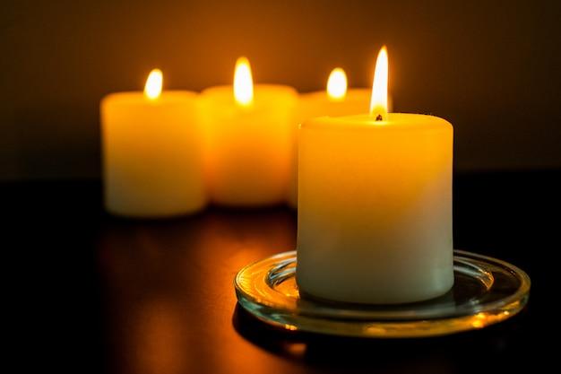 Primer plano de velas encendidas en la oscuridad