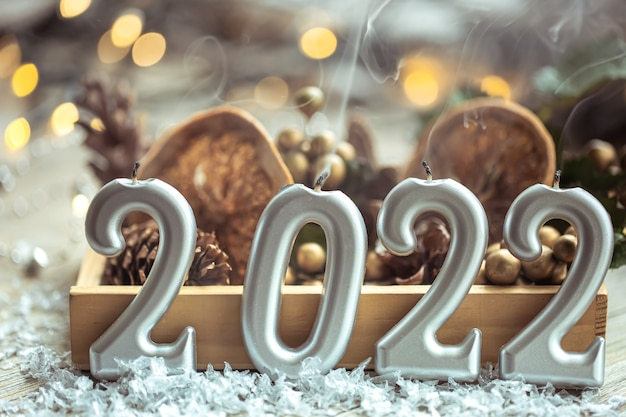 Primer plano de velas en forma de números 2022 sobre fondo borroso con decoración navideña y bokeh.