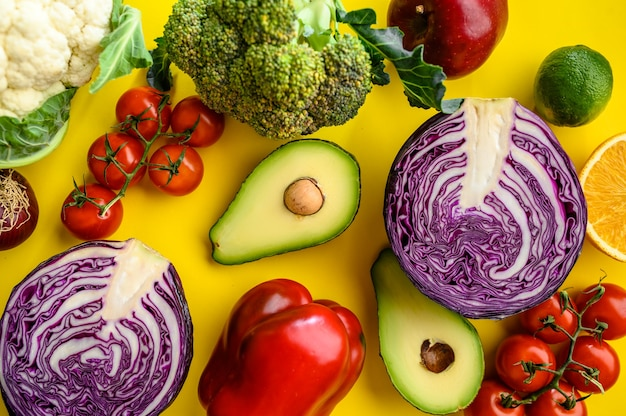 Primer plano de verduras y aguacate aislado en el cuadro amarillo. comida vegetariana orgánica, surtido de comestibles, productos ecológicos naturales, concepto de estilo de vida saludable