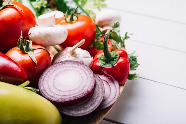 Primer plano de verduras crudas en mesa de madera