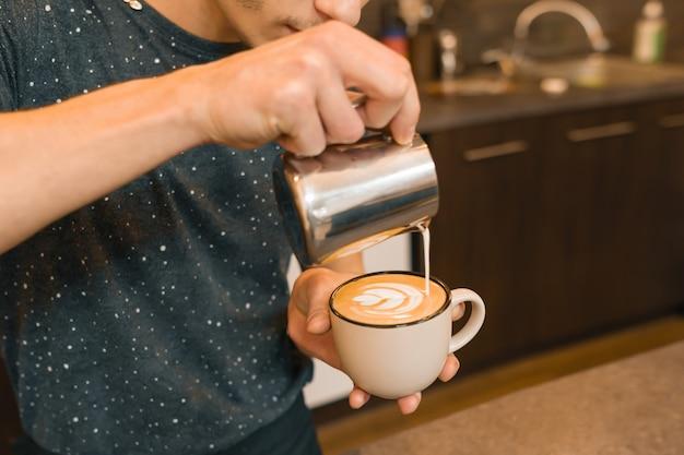 Primer plano de verter leche al vapor en la taza de café, fondo de cafetería