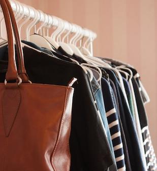 Primer plano vertical de una bolsa de cuero marrón y ropa colgada en perchas blancas