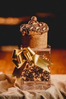 Primer plano vertical de una caja romántica con luces, una cinta dorada y un muffin
