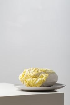 Primer plano vertical de una col napa en un plato sobre la mesa bajo las luces