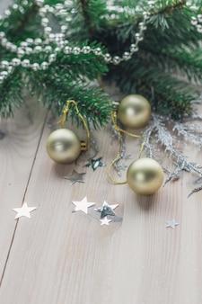 Primer plano vertical de coloridos adornos navideños en la mesa de madera bajo las luces