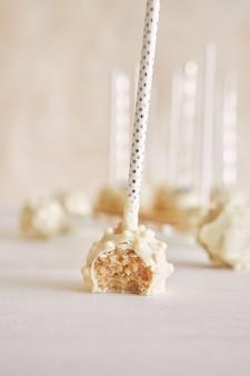 Primer plano vertical de delicioso pastel blanco aparece sobre una superficie blanca y mesa de madera