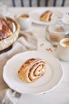 Primer plano vertical de deliciosos caracoles de nuez con café capuchino sobre la mesa de madera blanca