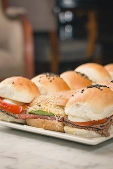 Primer plano vertical de deliciosos sándwiches en un plato blanco sobre una mesa de mármol