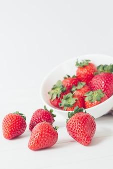 Primer plano vertical de fresas cerca de un recipiente blanco