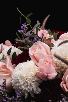 Primer plano vertical de un lujoso ramo de rosas rosadas y flores blancas