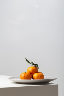 Primer plano vertical de mandarinas en un plato sobre la mesa bajo las luces sobre un fondo blanco.