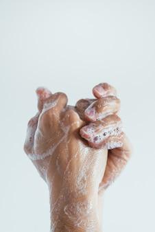 Primer plano vertical de las manos enjabonadas de una persona