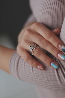 Primer plano vertical de una mujer con bonitas uñas vistiendo un hermoso anillo de plata