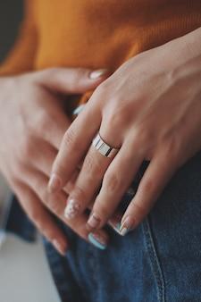 Primer plano vertical de una mujer en una camisa naranja con un costoso anillo de oro