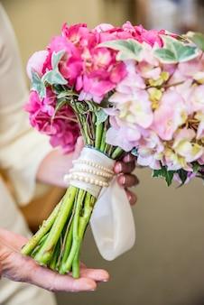 Primer plano vertical de la novia sosteniendo su elegante ramo de novia con flores rosas y blancas