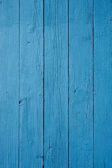 Primer plano vertical de una pared de madera pintada de azul bajo las luces