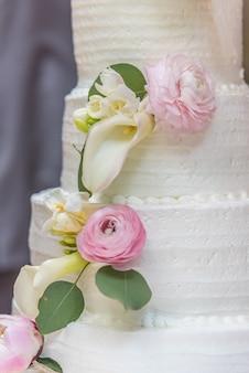 Primer plano vertical de un pastel de boda decorado con flores.