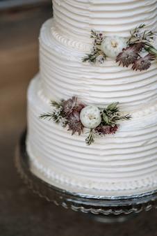 Primer plano vertical de un pastel de bodas de tres capas decorado con flores en bandeja de plata