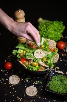 Primer plano vertical de una persona poniendo hierbas en la ensalada en un recipiente sobre la mesa bajo las luces