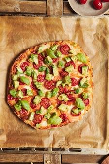 Primer plano vertical de una pizza con verduras en la mesa de madera