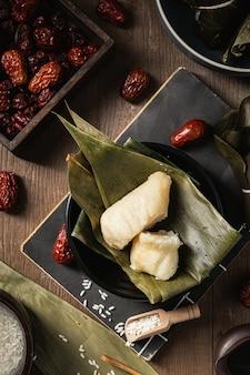 Primer plano vertical de preparación de bolas de masa de arroz con hojas de plátano