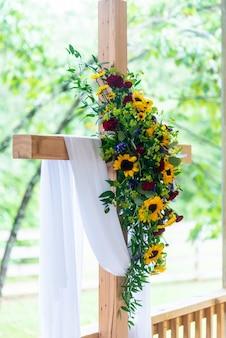 Primer plano vertical de un ramo de flores en una cruz de madera cubierta con una tela blanca