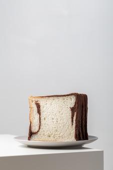 Primer plano vertical de rebanadas de pan blanco mezclado con chocolate en un plato sobre la mesa bajo las luces