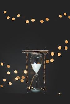 Primer plano vertical de un reloj de arena de cristal con luces quemadas en el fondo