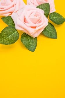 Primer plano vertical de rosas rosadas aislado sobre un fondo amarillo con espacio de copia