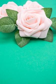Primer plano vertical de rosas rosadas aislado sobre un fondo verde con espacio de copia