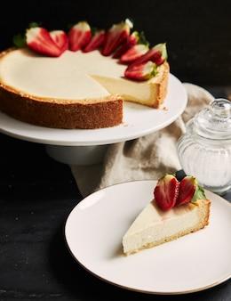 Primer plano vertical de una tarta de queso con fresa sobre una placa blanca.