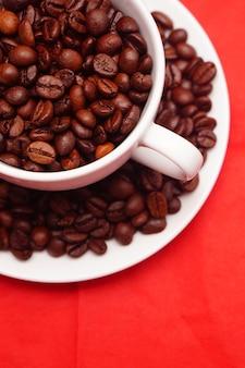 Primer plano vertical de una taza blanca llena de granos de café frescos en la mesa roja