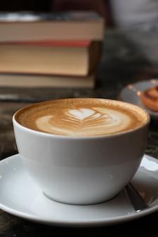 Primer plano vertical de una taza de café con leche cerca de algunos libros sobre una mesa