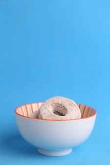 Primer plano vertical de un tazón de galletas caseras con azúcar en polvo contra un fondo azul.