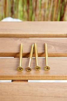Primer plano vertical de tornillos de cruz dorada sobre una mesa dorada