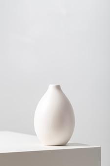 Primer plano vertical de una vasija de arcilla blanca sobre la mesa bajo las luces contra un blanco