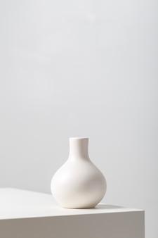 Primer plano vertical de una vasija de arcilla blanca sobre la mesa bajo las luces sobre un fondo blanco.