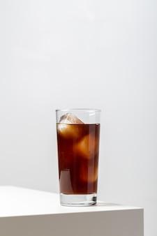 Primer plano vertical de un vaso de té helado en la mesa bajo las luces sobre un fondo blanco.