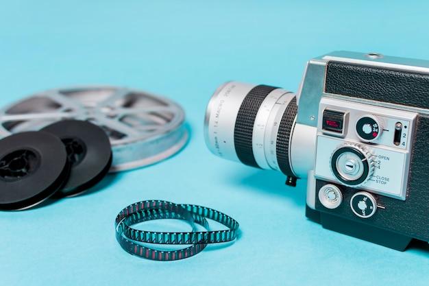Primer plano de la videocámara con rollos de película y tiras de película sobre fondo azul