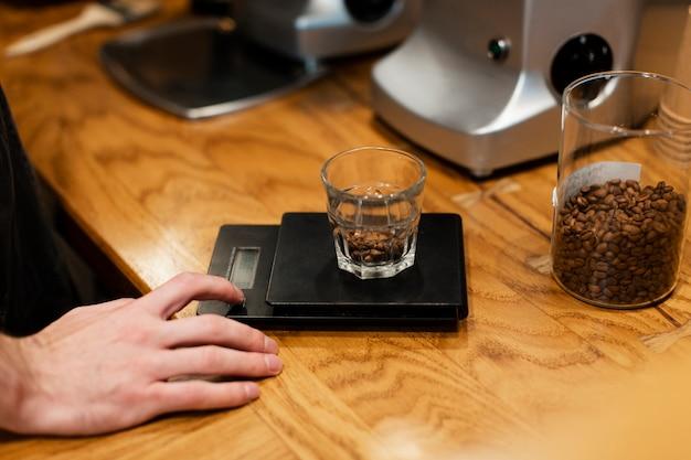 Primer plano de vidrio con granos de café en escala