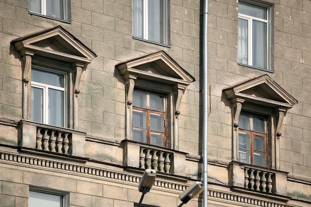 Un primer plano de viejas ventanas de piedra de un edificio de varios pisos de construcción soviética. fachada de una casa antigua