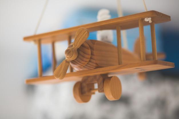 Primer plano de un viejo avión en miniatura de madera con un fondo borroso